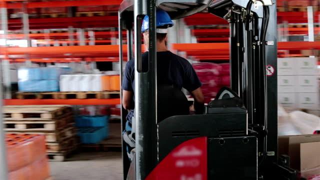 lagerarbeiter transportiert fertigprodukte mit einem gabelstapler. - hubwagen stock-videos und b-roll-filmmaterial