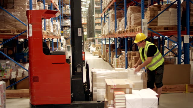 warehouse worker unpacking cardboxes from the forklift - macchinario edile video stock e b–roll