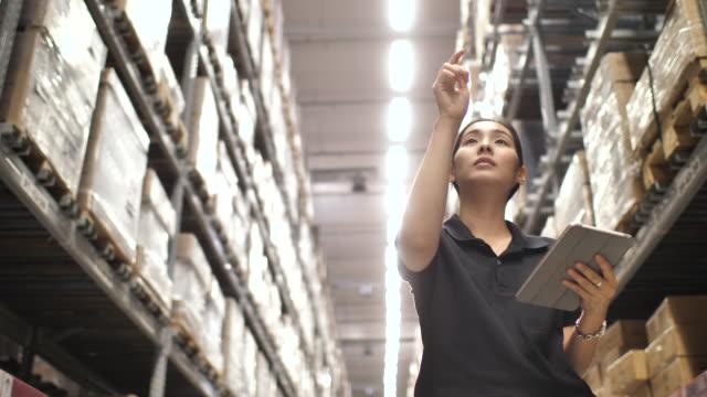 lagerarbeiter verwenden digitaltablett und notizen im notizblock im hintergrund des lagers - box container stock-videos und b-roll-filmmaterial