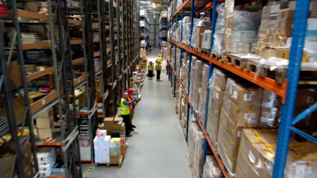 warehouse worker walking among shelves. supervising. drone point of view - deposito video stock e b–roll