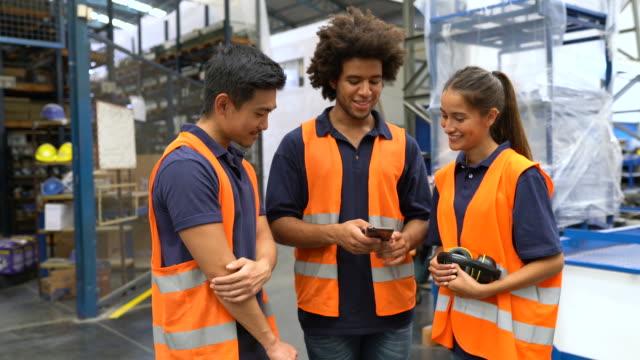 vídeos de stock e filmes b-roll de warehouse workers looking at a cell phone - trabalhador de armazém