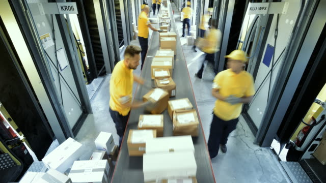 vídeos de stock e filmes b-roll de time-lapse warehouse workers placing packages on the conveyor belt - menos de 10 segundos