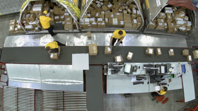 time-lapse warehouse workers putting packages onto the conveyor belt - conveyor belt stock videos & royalty-free footage