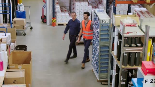 工場で歩く、話す倉庫労働者 - 倉庫作業員点の映像素材/bロール