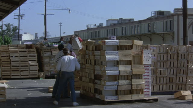 warehouse workers who are stacking crates dive out of the way of a speeding car. - 倉庫作業員点の映像素材/bロール