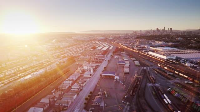 vídeos y material grabado en eventos de stock de almacenes y patio de carga cerca de la centro de la ciudad al atardecer - foto aérea - tren de carga