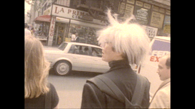 Warhol accompanied by director Russ Karel and a young woman walks his dog on a leash walks along E33rd St to his studios