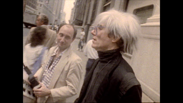 Warhol accompanied by director Russ Karel and a young woman walks his dog on a leash crosses 34th street at Madison Avenue / camera pans up to see...