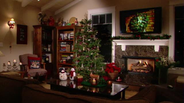 vídeos de stock e filmes b-roll de a warm fire burns in a fireplace in a living room decorated for christmas. - sala de estar
