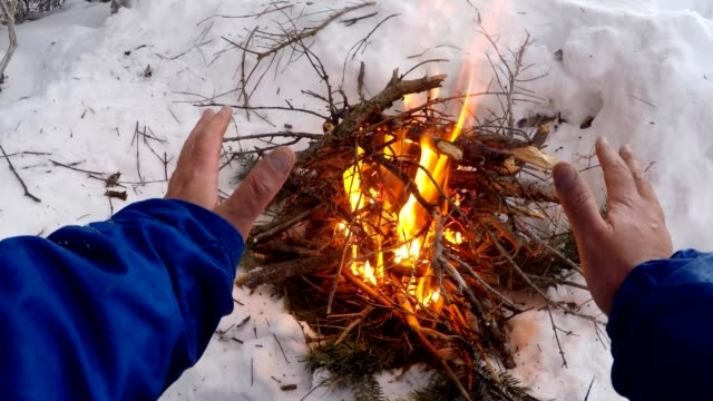 warming hand over fire in winter snow - survival stock videos & royalty-free footage