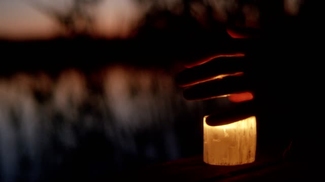 warming hands with a candle. lake sunset on a pier - decoration stock videos and b-roll footage