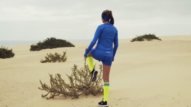 stockvideo's en b-roll-footage met opwarmen op een rotsachtige kust. bewolkt joggen - gymbroek