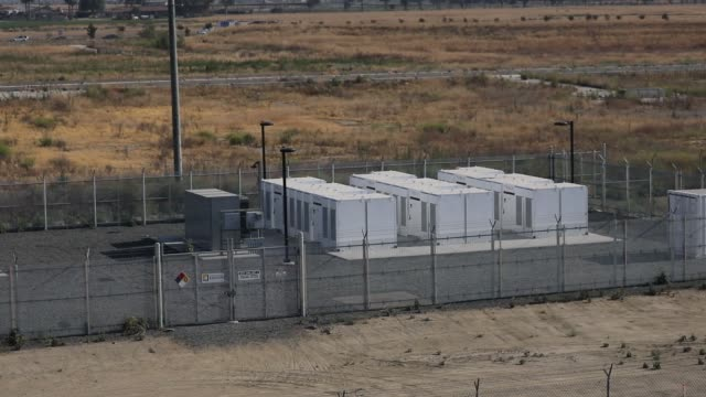 Warning and caution signs stand on display in front of the Tesla Inc Powerpack and inverter at the Southern California Edison Mira Loma Battery...
