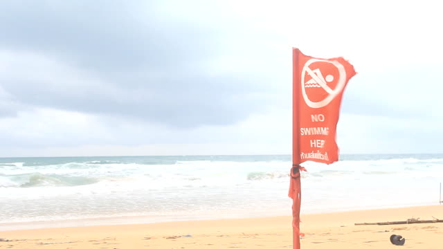 vídeos y material grabado en eventos de stock de bandera de advertencia de playa tropical rojo - marea
