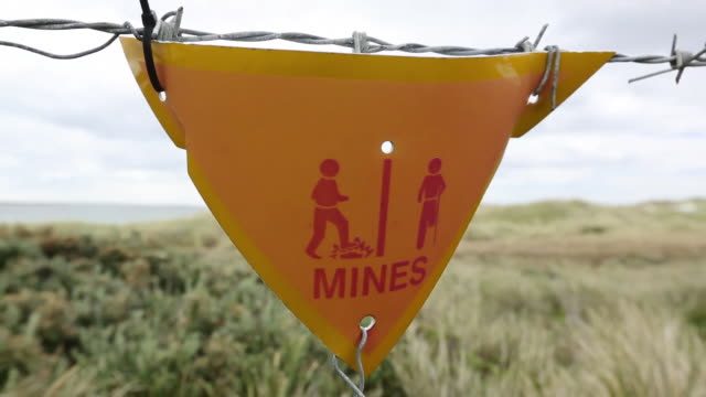 a warning sign about the presence of argentinian mines on the falkands, left over from the 1980's falklands conflict when argentina invaded the islands. - argentina america del sud video stock e b–roll