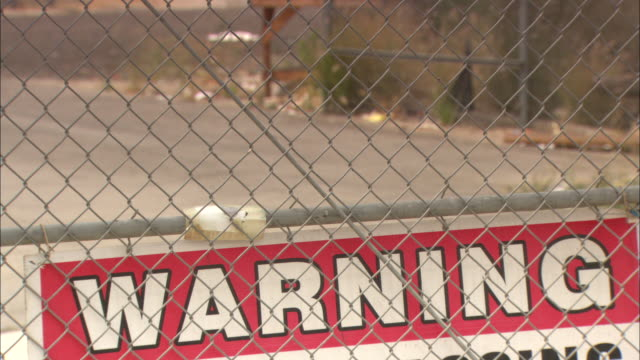 a warning sign hangs inside a chain-link fence. - warning sign stock videos & royalty-free footage