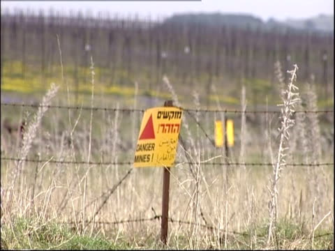 A warning sign hangs on a fence post at the edge of a mine field.