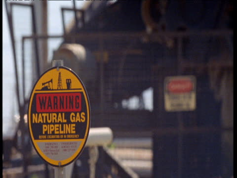 warning sign in front of nodding donkey oil pump, bakersfield, california - pipeline stock videos and b-roll footage