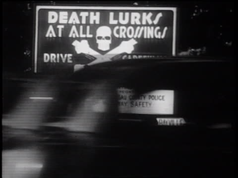 "B/W 1939 warning sign on highway: ""Death Lurks at all Crossings Drive Carefully"" / documentary"