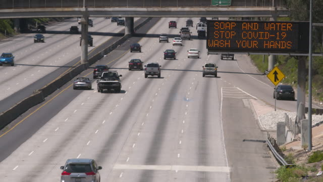 a covid-19 warning sign reminds drivers on a freeway in los angeles - road sign stock videos & royalty-free footage