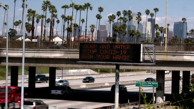a covid-19 warning sign reminds drivers on a freeway near downtown los angeles - message stock videos & royalty-free footage