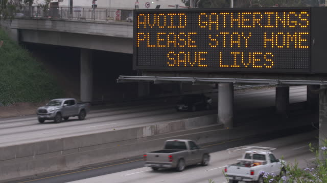 vidéos et rushes de a covid-19 warning sign reminds drivers on a freeway near downtown los angeles - autoroute