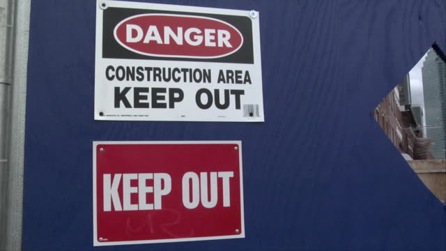 ms warning signs bolted to blue wall at construction site / new york, new york, usa - keep out sign stock videos & royalty-free footage