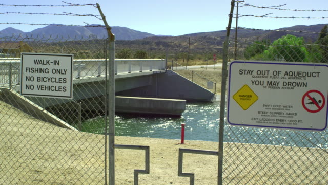 MS, Warning signs on fence at aqueduct, Palmdale, California, USA