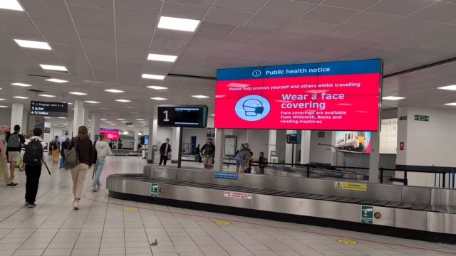 warning signs telling people to wear a face mask at the baggage arrival area at flight transport during coronavirus on july 29, 2020 in luton, england - luggage stock videos & royalty-free footage