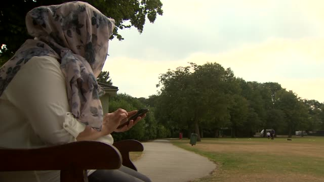 nspcc warning young people about risks of sexting england ext tree trunk pan blurred woman sitting **actor's voice overlaid sot** hands holding smart... - headscarf stock videos & royalty-free footage