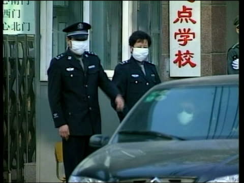 warning/cases and deaths increase; itn china: beijing: ext man suspected to be suffering from sars helped along street towards hospital by friend... - 重症急性呼吸器症候群点の映像素材/bロール