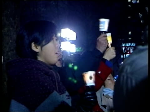 warnings over economic sanctions itn south korea seoul ext at night cs candle held during antiamerican protest ms people taking part in antiamerican... - attending stock videos and b-roll footage