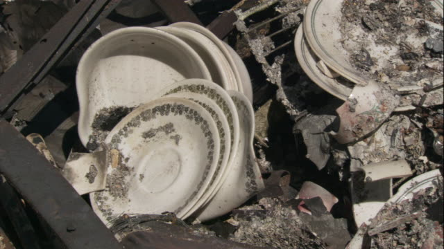 warped plates rest in the ashes of a burned building after the eyre peninsula bushfire. - kitchenware department stock videos and b-roll footage