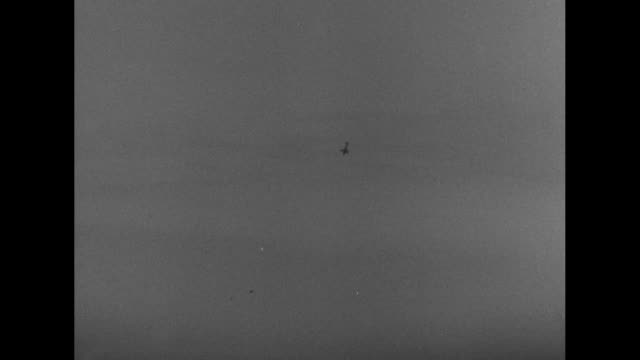 vídeos y material grabado en eventos de stock de warplanes flying in formation overhead / expansive view of a harbor and ocean beyond / an airplane swoops in and drops bombs which explode around a... - world war ii