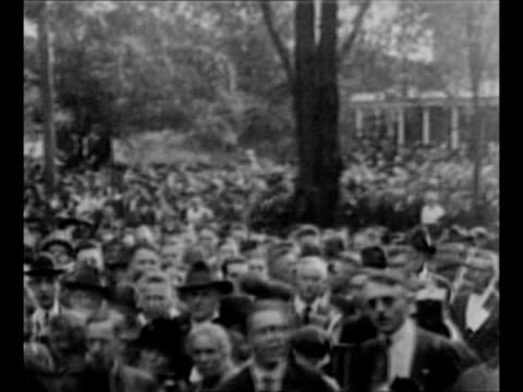 Warren and Florence Harding come out of house onto porch wave as they campaign for Harding's election to the US presidency / pan crowd in front of...