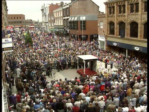 warrington memorial services major in ulster ext tgv mass open air service with mass crowds cbv woman wiping eyes as baby looking over another... - mitten stock videos and b-roll footage