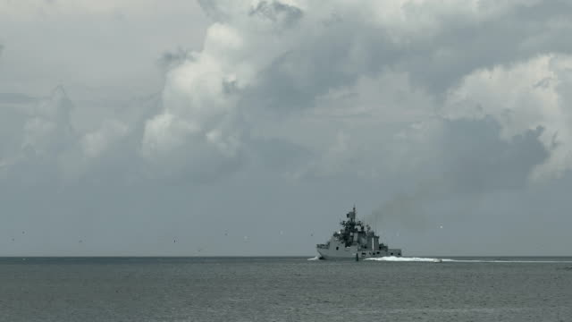 warship in the background of a cloudy sky - warship stock videos & royalty-free footage