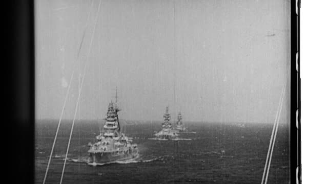 Warships and aircraft of an Imperial Japanese Navy task force demonstrate their prowess when they leave a harbor and practice naval gunnery at sea