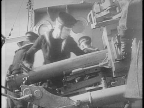 Warship's crew loads artillery guns on deck / man in booth phones gun crew / gunfire erupts from ship / sailor in windsuit and hood looks through...