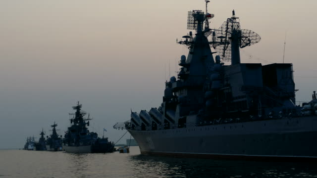 warships in the bay at anchor at sunset