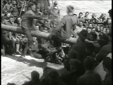 Warships on ocean Soldiers having pillow fight on ship's railing Soldiers exercising on deck eating at mess table