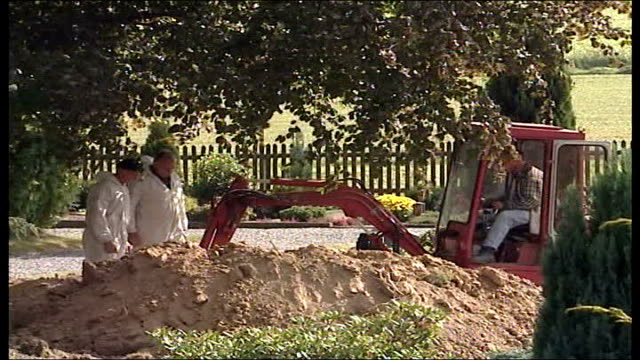 wartime children's mass grave discovered men watching bulldozer at work man standing in grave with retrieval equipment - mass grave stock videos and b-roll footage