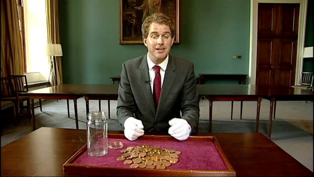 wartime treasure found in hackney; england: london: int close up of hoard of gold coins pile of gold coins on tray next empty jam jar close ups of... - change stock videos & royalty-free footage