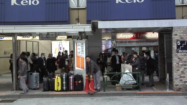 vídeos y material grabado en eventos de stock de wary travellers waiting for the airport bus at shinjuku terminal - escritura occidental