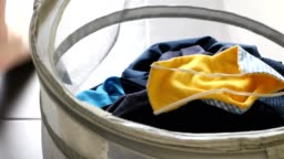 Washable homemade face mask being thrown in dirty laundry basket