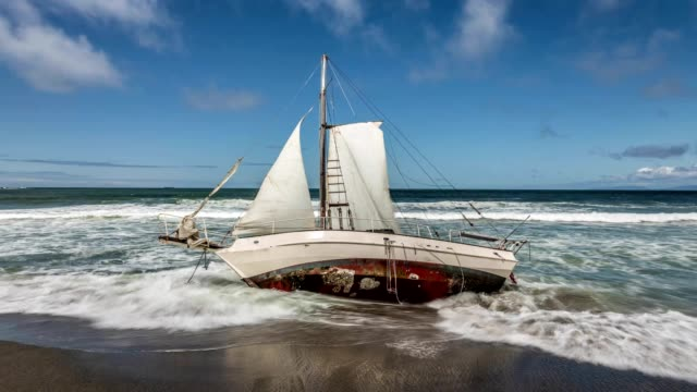 stockvideo's en b-roll-footage met zeilboot aangespoeld op strand - scheepswrak