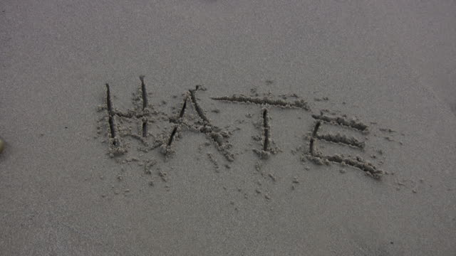 stockvideo's en b-roll-footage met 'hate' washed away on the beach - racisme