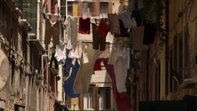 vídeos de stock e filmes b-roll de washing drying on lines across a street in venice - itália