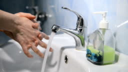 washing hands under running water with liquid soap