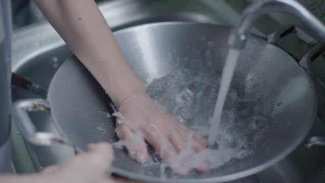 vídeos de stock, filmes e b-roll de lavagem de utensílios de cozinha - lavando louça